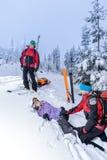 Ski patrol helping woman with broken leg stock photos