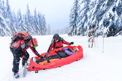 Ski patrol with rescue sled injured woman Stock Image