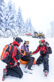 Ski patrol team rescue woman broken arm. Ski patrol team rescue women skier with broken arm Royalty Free Stock Photography