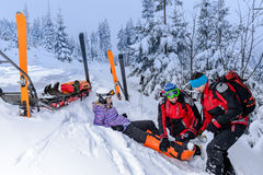 Ski patrol team rescue woman broken leg Royalty Free Stock Images