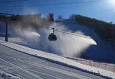 Ski piste and gondola lift and snow guns operating. Ski piste with gondola lift and snow guns operating Royalty Free Stock Image