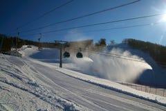 Ski piste and gondola lift and snow guns operating. Ski piste with gondola lift and snow guns operating Stock Photo