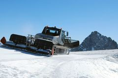 Ski piste snow groomer machine on mountain Royalty Free Stock Image