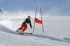 Ski racer and a red gate at a slalom competition Stock Photography