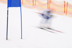 Ski racer runs by blue slalom gate Royalty Free Stock Photography