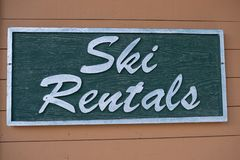 Ski rentals wooden sign on the building stock images