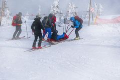 Ski rescue team with slide stretcher, brings help royalty free stock image
