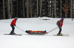 Ski rescuers are transporting injured skier. Along a slope on February 19, 2011 in Bukovel ski resort, Ukraine Royalty Free Stock Photos