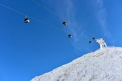 Ski resort with cable cars or aerial lift and ski-lift moving ab royalty free stock image