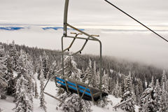 Ski Resort Chairlift. A ski resort chairlift sits above the trees below as a low fog clings to the treetops Stock Images