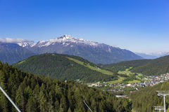 Ski resort in fall. With green slopes and snowy mountains in the back Royalty Free Stock Photography