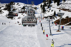 Ski resort infrastructure. Chair lifts and skiers using ski lifts at ski resort Stock Photos