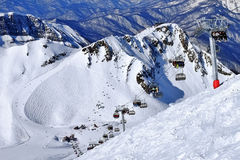 Ski resort in mountains. Lopes and ski lift in a big mountains Royalty Free Stock Photo