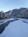 Ski Resort Rosa Khutor, Russia. Snowy stream, hotel buildings and parking on the waterfront, mountains with ski slopes, winter in Krasnaya Polyana, Russia Royalty Free Stock Photos