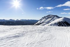 Ski resort.Ski slopes.Sunny day at the ski resort.Panoramic view on snowy off piste slope for freeriding with traces from skis, sn. Owboards and blue sky with Stock Photography