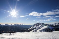 Ski resort.Ski slopes.Sunny day at the ski resort.Panoramic view on snowy off piste slope for freeriding with traces from skis, sn. Owboards and blue sky with Stock Image