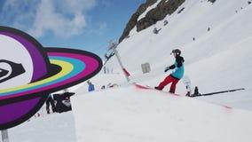 Ski resort. Teen snowboarder jump on springboard. Cardboard cosmic objects. Sun stock video
