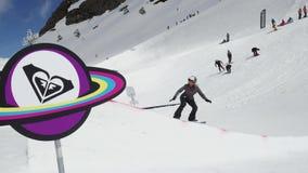 Ski resort. Teen snowboarder jump from springboard. Sun. Cardboard cosmic object stock video
