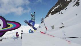 Ski resort. Teen snowboarder jump on springboard. Sunny. Cardboard cosmic object stock video