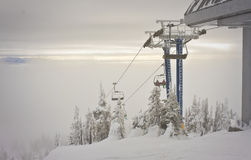 Ski Resort Top of Chairlift. A foggy day on the mountain from the top as the sun pokes through the clouds behind Royalty Free Stock Images