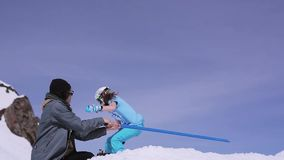 Ski resort. Trainer hold blue stave as springboard for snowboarders. Mountains stock video