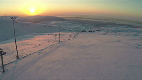Ski-run and snowy hills at sunset, aerial view stock footage