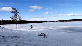 Ski simple de femme dans le lac congelé sous le ciel bleu et le nuage blanc clips vidéos