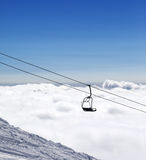 Ski slope, chair-lift and mountains under clouds Stock Images
