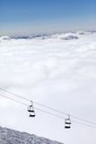 Ski slope, chair-lift and mountains under clouds Royalty Free Stock Photo