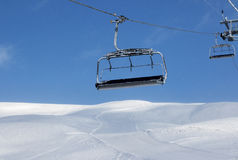 Ski slope, chair-lift on ski resort and blue sky with falling sn Royalty Free Stock Image
