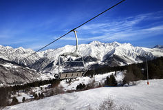 Ski slope and chair-lift in snow winter mountains at sun windy d Stock Images