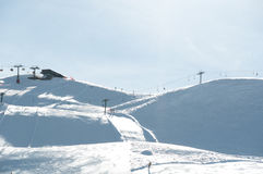 Ski slope with chairlifts. Pretty empty ski piste with chairlifts and station in the background - shot in Livigno, Italian Alps Royalty Free Stock Photo