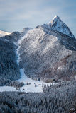 Ski slope at the foot of the mountains in winter Stock Photography