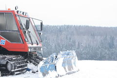 Ski Slope Grooming Tractor. A view of the front end of a tracked vehicle used to prepare and groom ski slopes for skiing in the winter royalty free stock photo