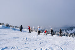 Ski slope, people skiing down the hill, mountains view, fog Stock Photography