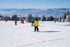 Ski slope, people skiing down the hill, mountains view Stock Image