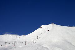 Ski slope with ropeway at sun winter day Royalty Free Stock Photo