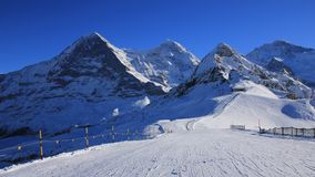 Ski slope and snow covered mountaind Eiger, Monch, Lauberhorn an Royalty Free Stock Photography