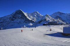 Ski slope and snow covered mountains Eiger, Monch, Lauberhorn an Stock Photography