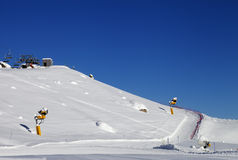 Ski slope with snowmaking at sun day Stock Images