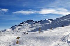 Ski slope with snowmaking at sun morning Royalty Free Stock Image