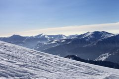 Ski slope with trace of ski, snowboards and mountains in haze Royalty Free Stock Photography