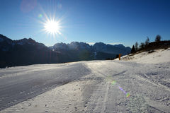 The ski slope with a view on Dolomiti mountains and sun Royalty Free Stock Photo