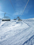 Ski slopes from chairlift. View on a wide snowy winter landscape from a high chairlift in the swiss alps royalty free stock photos