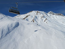 Ski slopes on sunny day. Chairlift on Ski slopes on sunny day in Austrian alps Royalty Free Stock Image