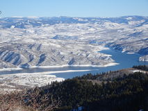:Ski slopes in Wyoming. Snow covered mountains overlooking a blue lake stock photos
