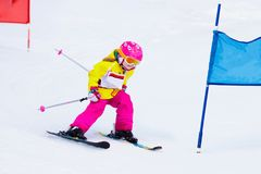 Ski and snow fun. Kids skiing. Child winter sport. Child skiing in mountains. Active toddler kid with safety helmet, goggles and poles. Ski race for young stock image