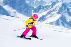 Ski and snow fun. Kids skiing. Child winter sport. Child skiing in mountains. Active toddler kid with safety helmet, goggles and poles. Ski race for young royalty free stock photos