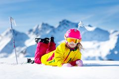 Ski and snow fun. Kids skiing. Child winter sport. Child skiing in mountains. Active toddler kid with safety helmet, goggles and poles. Ski race for young royalty free stock photography