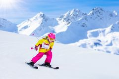 Ski and snow fun. Kids skiing. Child winter sport. Child skiing in mountains. Active toddler kid with safety helmet, goggles and poles. Ski race for young royalty free stock photo